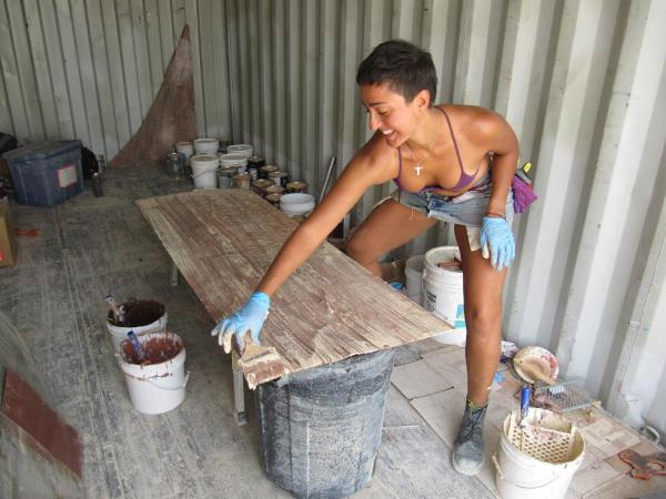 Andrea, hiding from a dust storm in the container, painting sheets of bark.