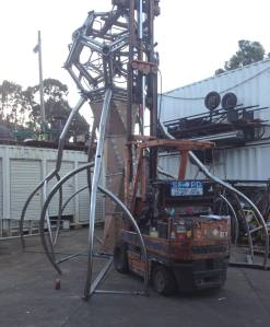 the upper dodeca neuron, with its ground dendrites, is supported by the forklift while the fab crew makes measurements