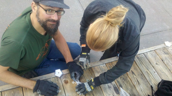 Adriaan and Siobhan remove a stripped out wood screw from the decking.